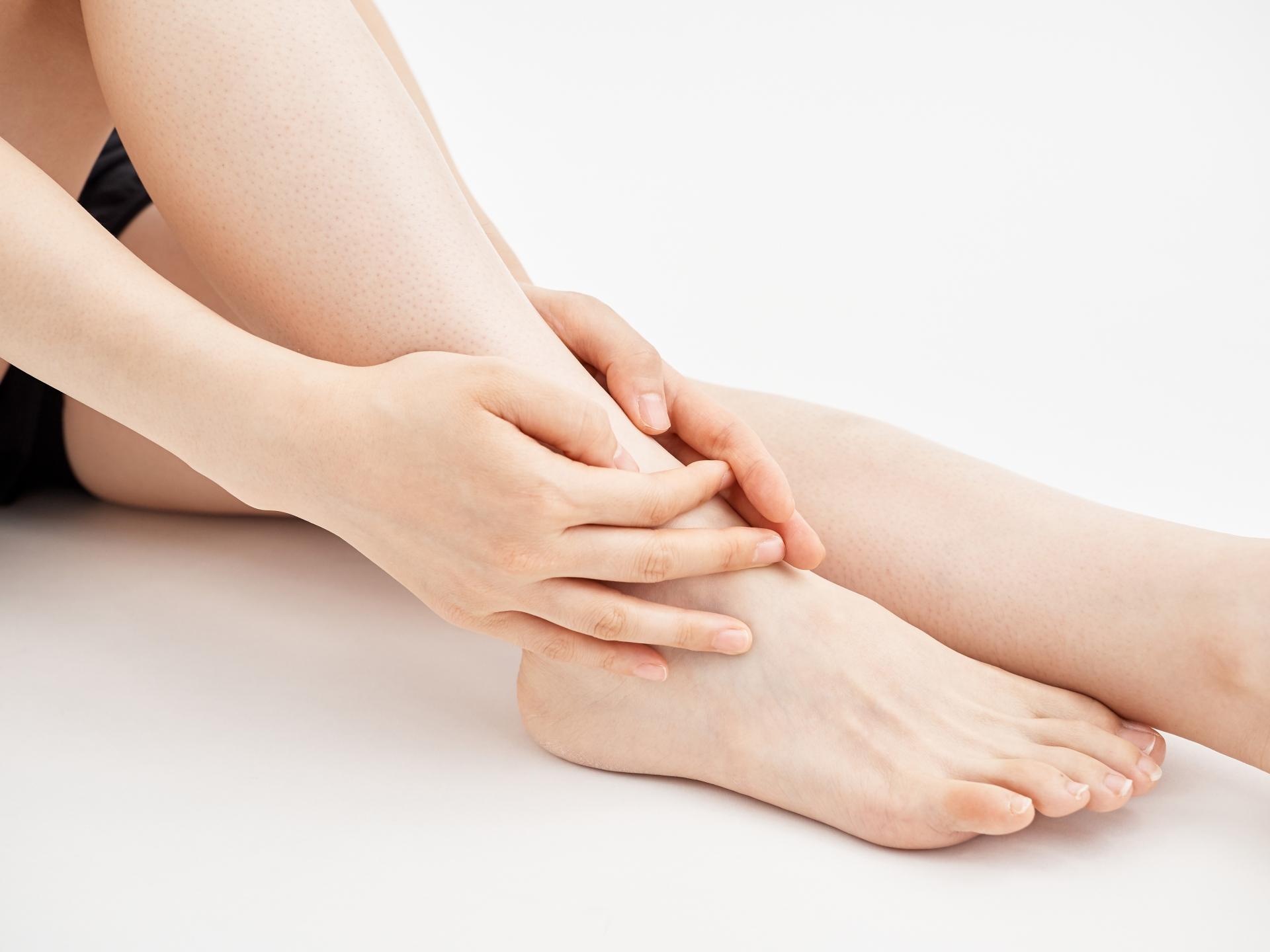 白背景で痛い足の関節を押さえる女性